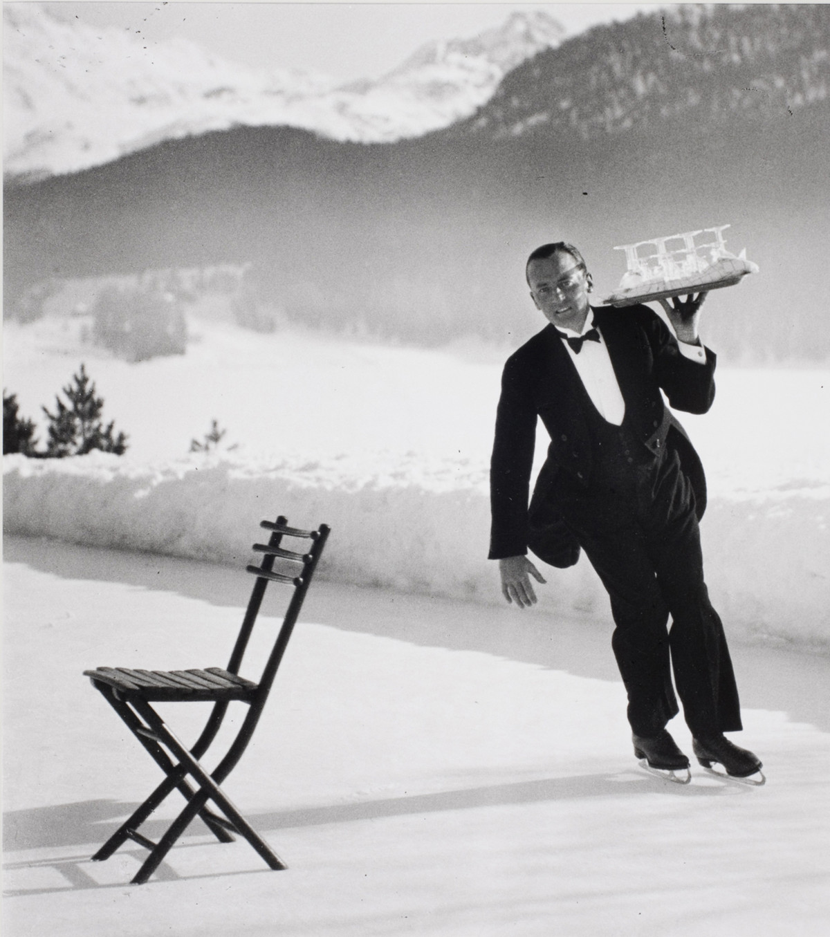Senior waiter René Breguet from the Grand Hotel serving ice skating cocktails. The commune of St. Moritz in Switzerland, 1932.