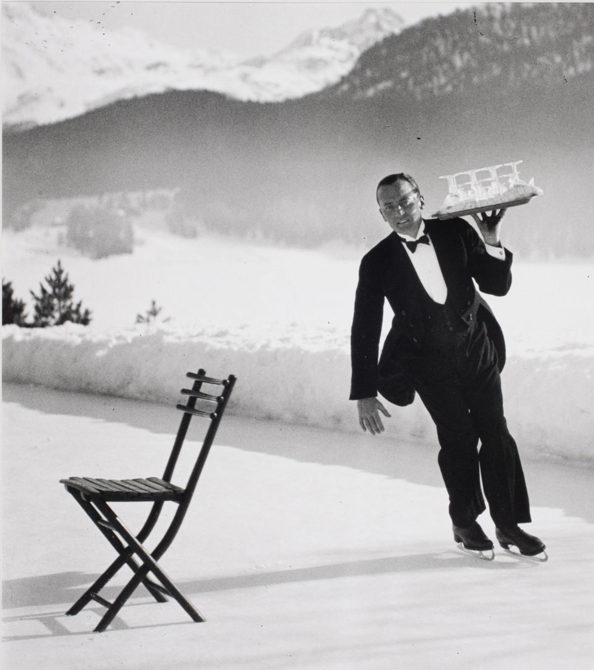 Senior waiter René Breguet from the Grand Hotel serving ice skating cocktails. The commune of St. Moritz in Switzerland, 1932.
