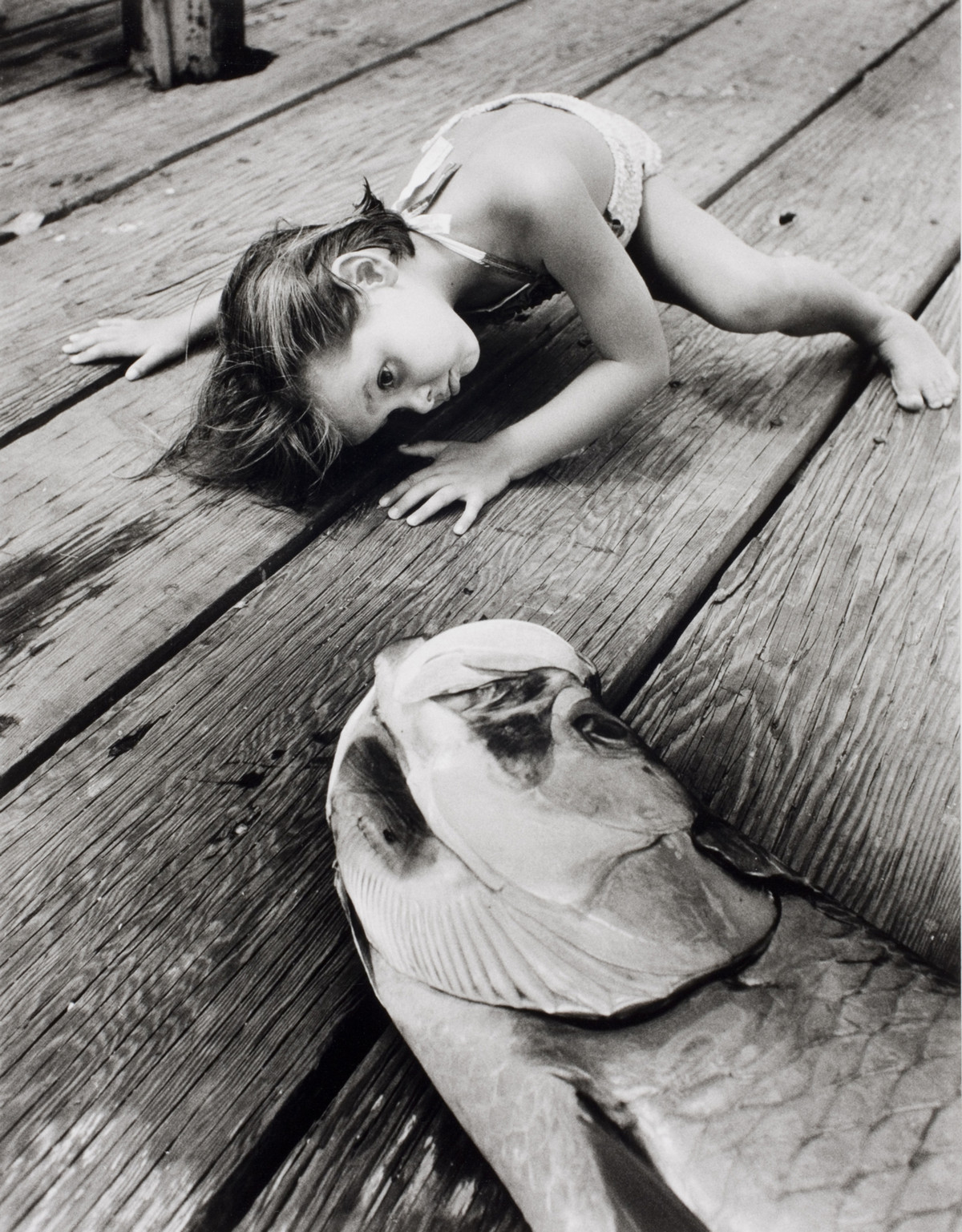 Alfred Eisenstaedt photos of a girl Looks into the mouth of a big fish that dad just caught. Florida, USA, 1956.