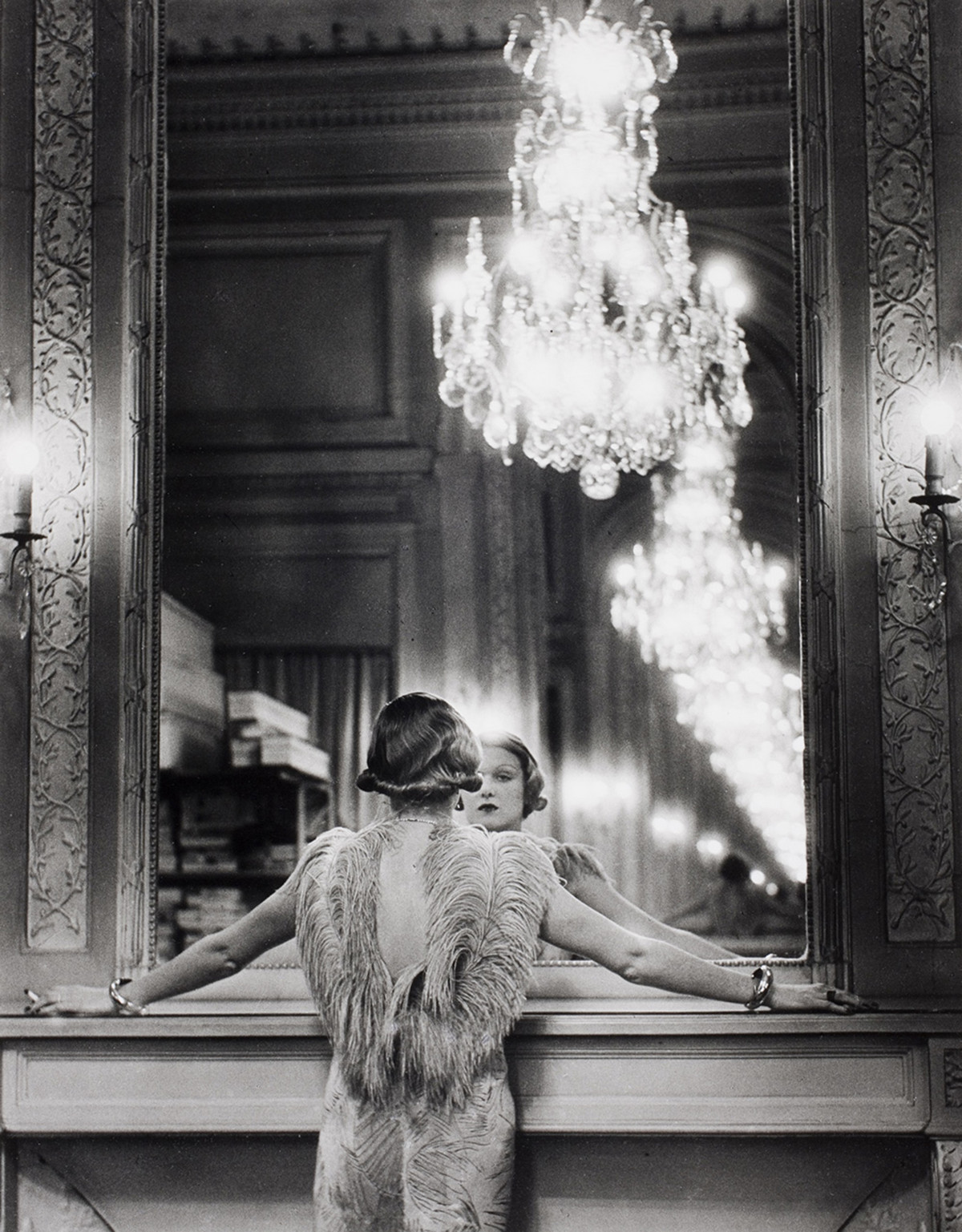 Model looking into a large mirror, Paris, France, 1932.