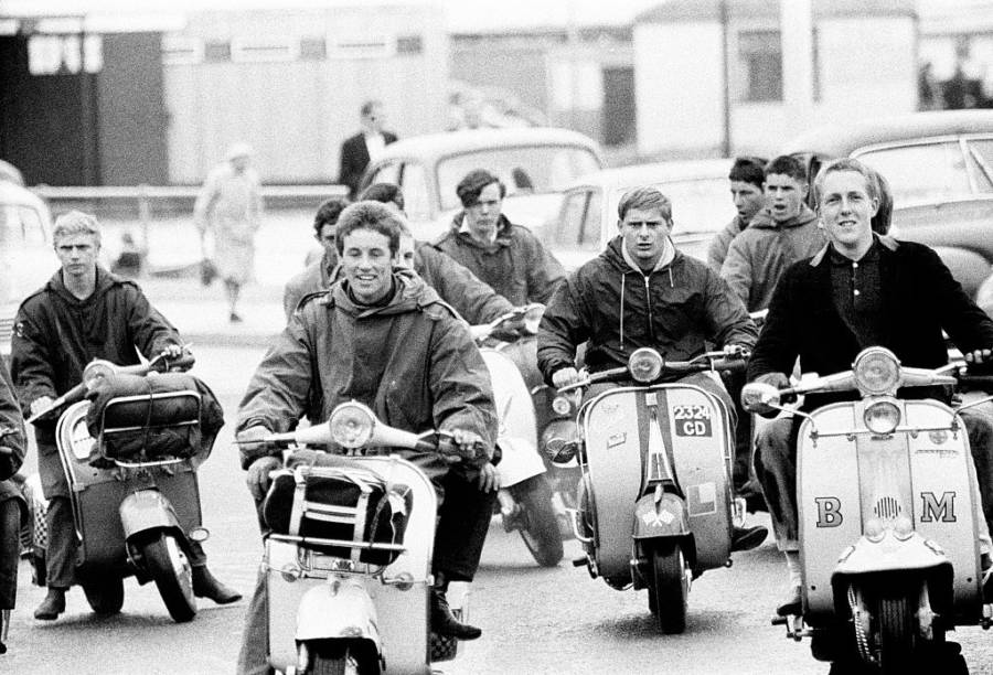 Mods on scooters ride down the streets of England.