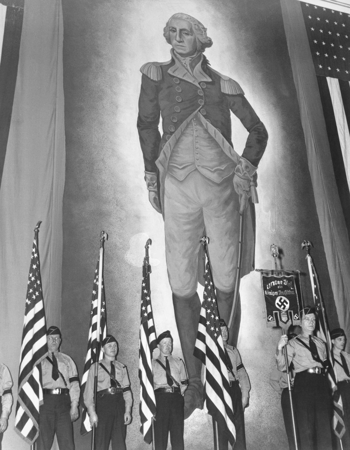 Nazi guards in front of a huge portrait of George Washington.
