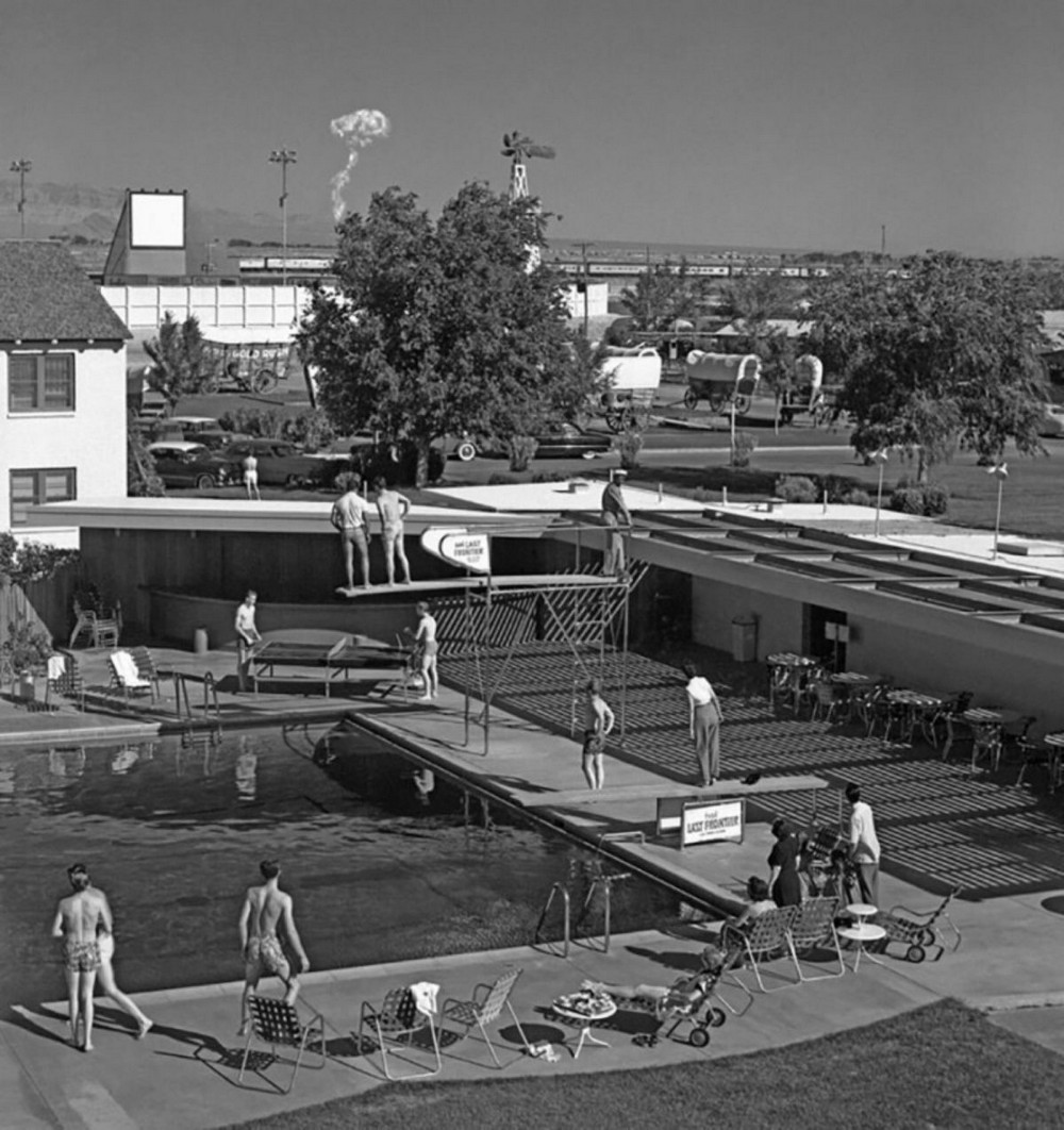 Swimmers at the pool in a Las Vegas hotel watch a cloud from a nuclear explosion at a testing site 120 kilometers from the hotel, 1953