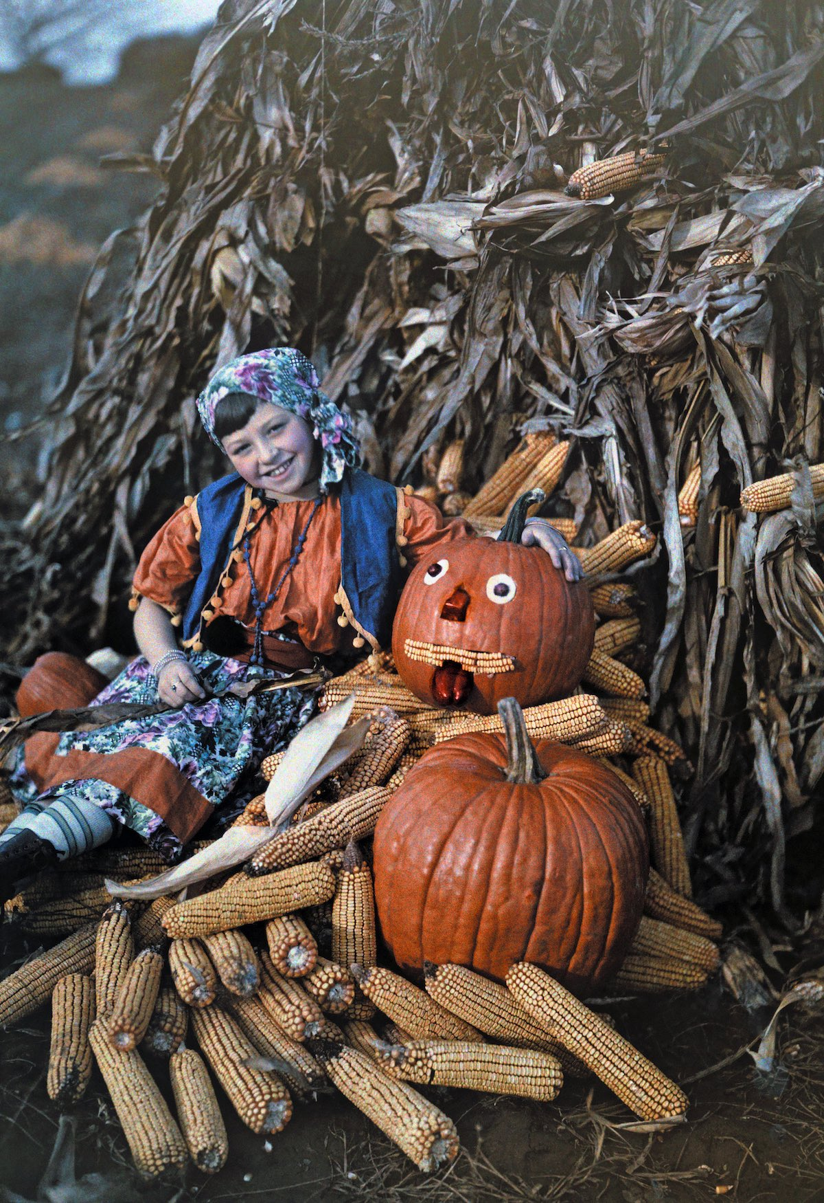 Virginia - A girl poses with corncobs and pumpkins during the harvest