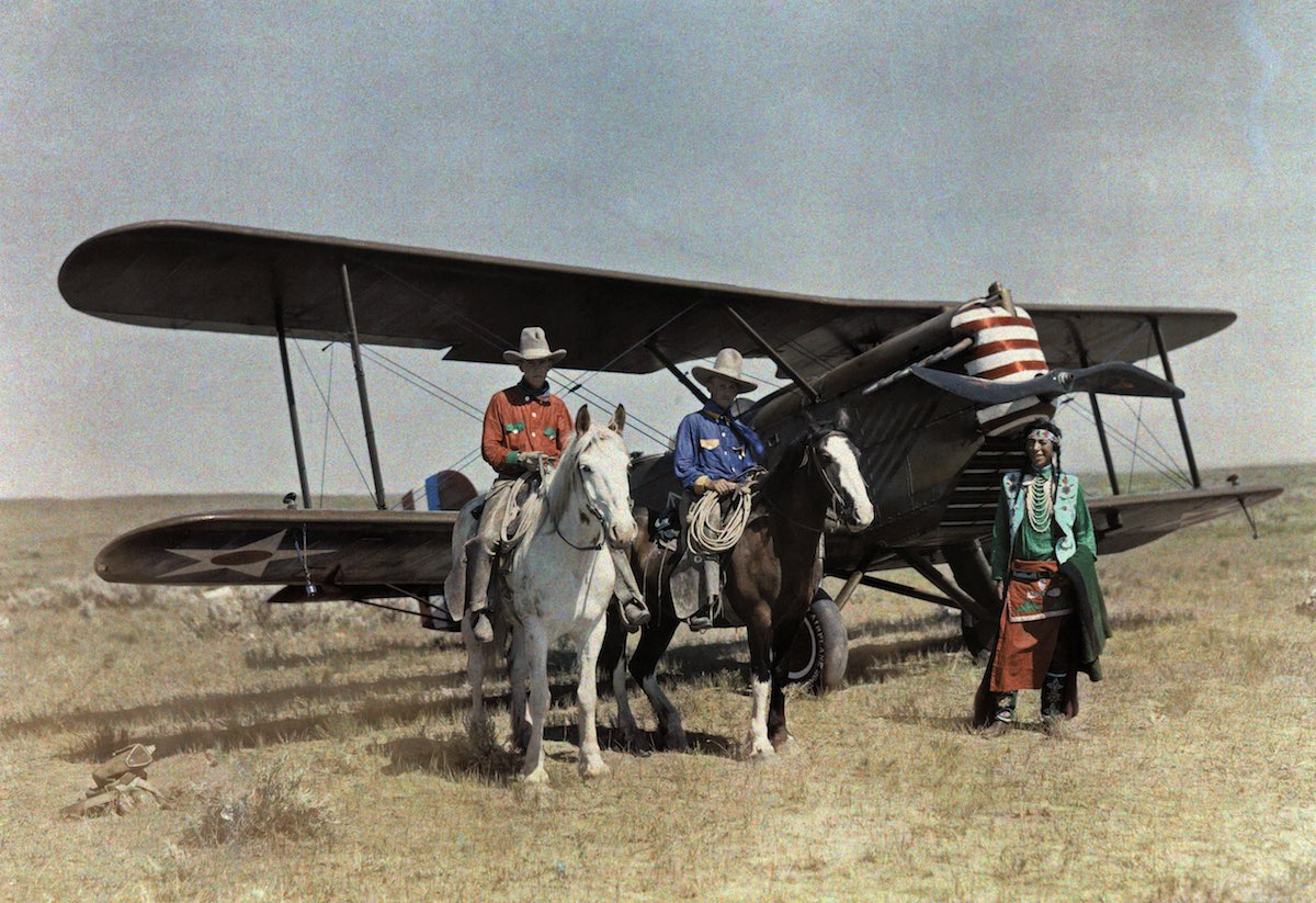 Three men stand in front of a plane on the Crowe Reservation in Montana