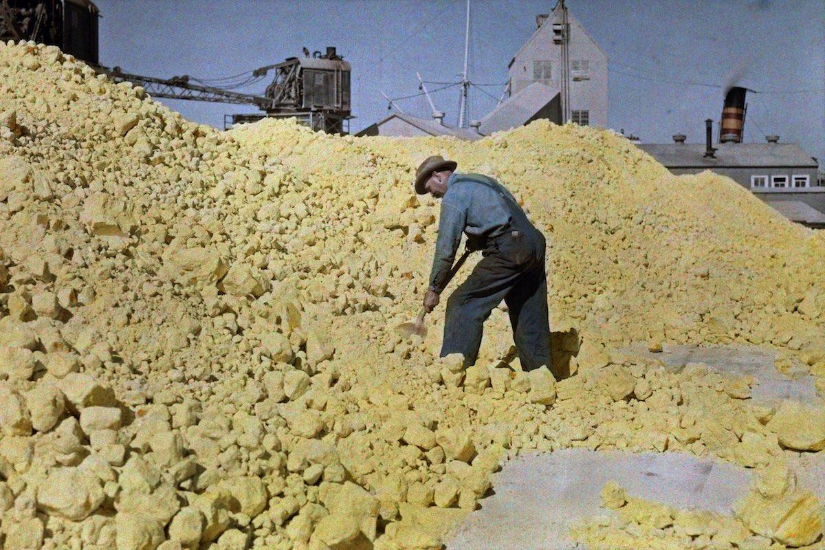 A man shovels sulfur in a warehouse near the pier, Galveston, Texas.