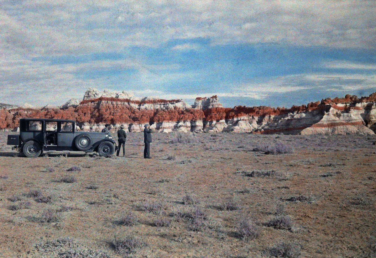 Hopi Indian Reservation - Men stand next to a car in a field and look at a nearby canyon.