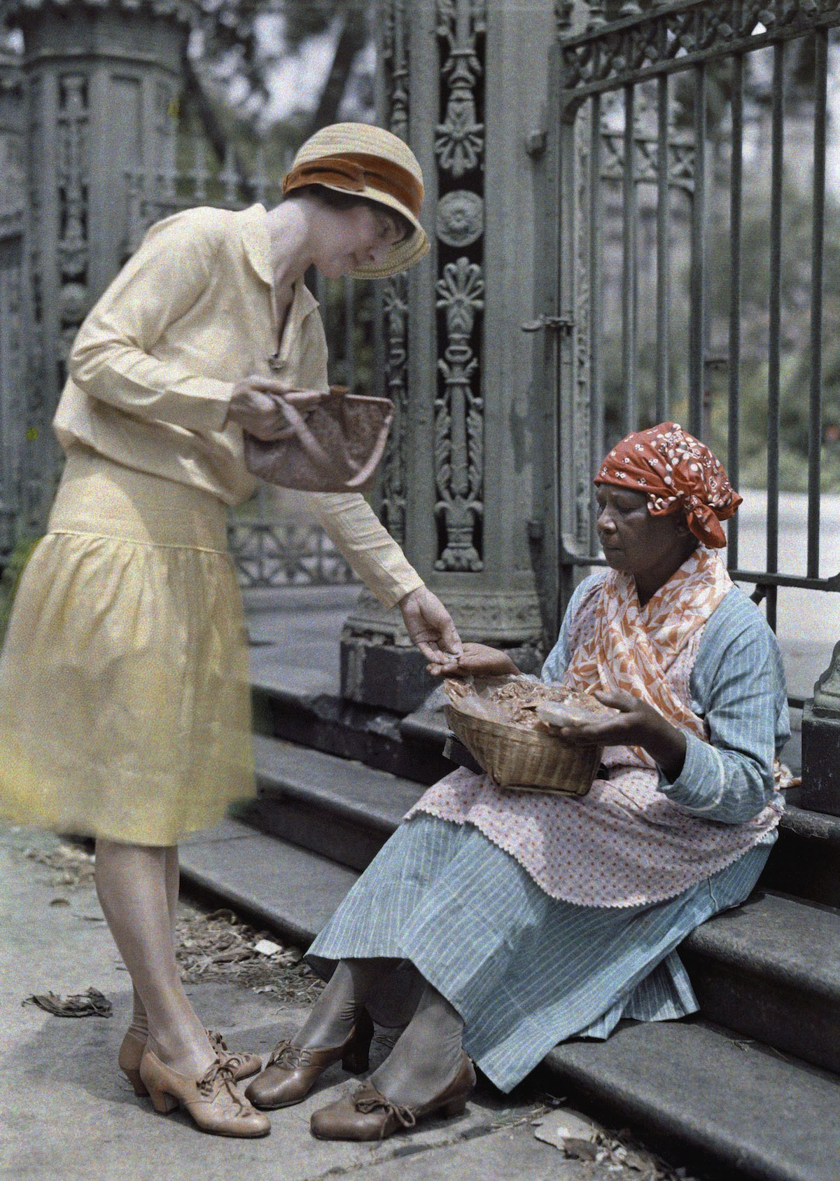 A woman sitting on stone steps in the French Quarter sells pralines.