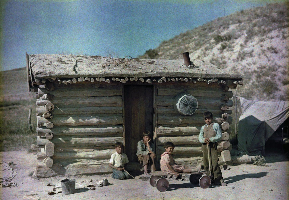 Pine Ridge Indian Reservation, South Dakota. Kids outside a house with a turf roof.